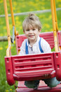 Little boy on a swing in nature Stock Images