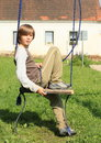 Little boy on a swing sitting Stock Image