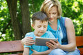 Little boy with tablet in the hand playing mother wireless technology outdoor Stock Image