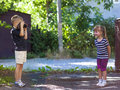 Little boy taking the picture of a litthe girl on sunny summer d Royalty Free Stock Photo