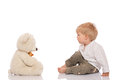 Little boy and teddy bear with blond hair sitting on the floor looking at her isolated on white background Stock Photo