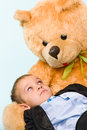Little boy and teddy bear posing playing with a on studio light blue background Royalty Free Stock Photography