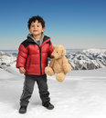 Little boy with teddy bear in the snow Royalty Free Stock Photos