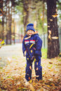 Little boy throws the autumn leaves in the air happy Stock Image