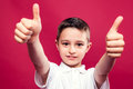 Little boy with thumbs up over a reed background Stock Photo