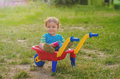 Little boy toddler playing with colorful children's plastic building wheelbarrow Royalty Free Stock Photo