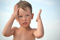 The little boy is too hot in the sun without a hat the child has a headache the child holds his head shows that headache spinning Royalty Free Stock Photos