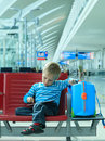 Little boy with touch pad waiting in the airport travel concept Stock Photography