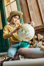 Little boy traveler in hat holding globe while sitting on porch