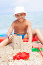 Little boy at tropical beach making sand castle Royalty Free Stock Photo