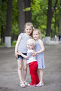 Little boy and two older cousins meeting in the summer park blonde sisters Royalty Free Stock Photos