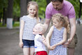 Little boy and two older cousins meeting in the summer park blonde sisters Stock Photo