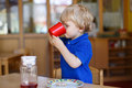 Little boy of two years having breakfast at nursery blond Stock Image