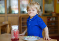 Little boy of two years having breakfast at nursery blond Stock Images