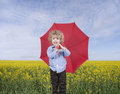 Little boy umbrella standing front oilseed field Royalty Free Stock Photography