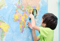 Little boy using magnify looking on map in classroom Royalty Free Stock Photography