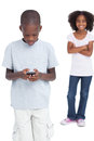 Little boy using mobile phone with his sister behind him Stock Photos