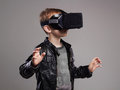 Little Boy in virtual reality glasses playing the game