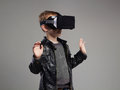 Little Boy in virtual reality glasses playing the game. kids fun