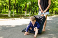 Little boy waiting with his mother in a country road sitting in an open suitcase on the asphalt Royalty Free Stock Images