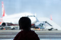 Little boy watching planes at the airport standing in silhouette with his back to camera a large window overlooking Stock Photos
