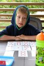 Little boy wearing hood playing cards Royalty Free Stock Photo