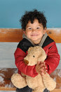 Little boy wit teddy bear seated on a bench Stock Photos