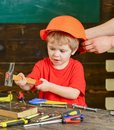 Little boy working with hammer. Daddy taking care of sons safety. Male hands holding orange protective helmet. Small kid Royalty Free Stock Photo