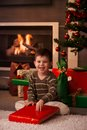 Little boy wrapping out christmas present happy sitting on floor in front of tree and fireplace Stock Image