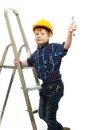Little boy with wrench tool in protective helmet on a ladder Royalty Free Stock Photography