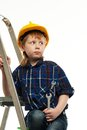 Little boy with wrench tool in protective helmet on a ladder Royalty Free Stock Images