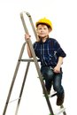 Little boy with wrench tool in protective helmet on a ladder Stock Image