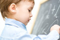Little boy is writing on blackboard Royalty Free Stock Photo