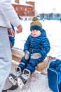 Little boy 3-5 years old, sitting on a bench for shoes, in the winter in a city park on a snow-covered skating rink. In Royalty Free Stock Photo