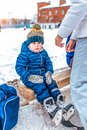 Little boy 3-5 years old, sitting on a bench, in the winter in the city on a public skating rink. In blue overalls and a Royalty Free Stock Photo