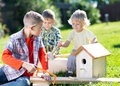 Little boys friends making wooden nest box in summer green park Royalty Free Stock Photo