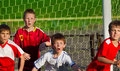 Little boys playing soccer sports field next to goal Royalty Free Stock Image