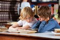 Little boys reading book together in library while sitting at table with classmates background Stock Image