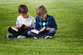 Little boys sitting on the grass in a park and reading books. Education, lifestyle, people concept Royalty Free Stock Photo