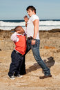 Little brave one dwarfish african men figthing with an young caucasian men on the rocky beach Stock Photos