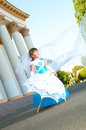Little bride a girl in a lush white and blue wedding dress veil Stock Photography