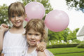 Little bridesmaids holding party balloons in garden portrait of cute with Stock Photography