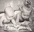 Little brother and sister looking at a book while lying on bed Royalty Free Stock Images