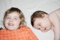 Little brother and sister smile and lie pretty on white sheet on bed focus on boy Royalty Free Stock Photography