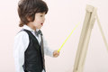Little brunet boy with yellow pointer stands near wooden easel in studio Royalty Free Stock Image