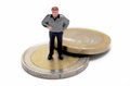 Little budget miniature man figure over euro coins Royalty Free Stock Images
