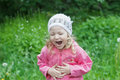 Little Caucasian girl bending with belly laughter in spring green garden Royalty Free Stock Photo