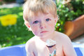 Little caucasian toddler boy eating ice cream in cone