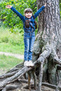 Little cheerful girl teetering on the roots of a tree with two plaits large selective focus Royalty Free Stock Images