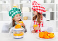 Little chef girls tasting the orange juice they made fresh healthy nutrition concept Royalty Free Stock Image